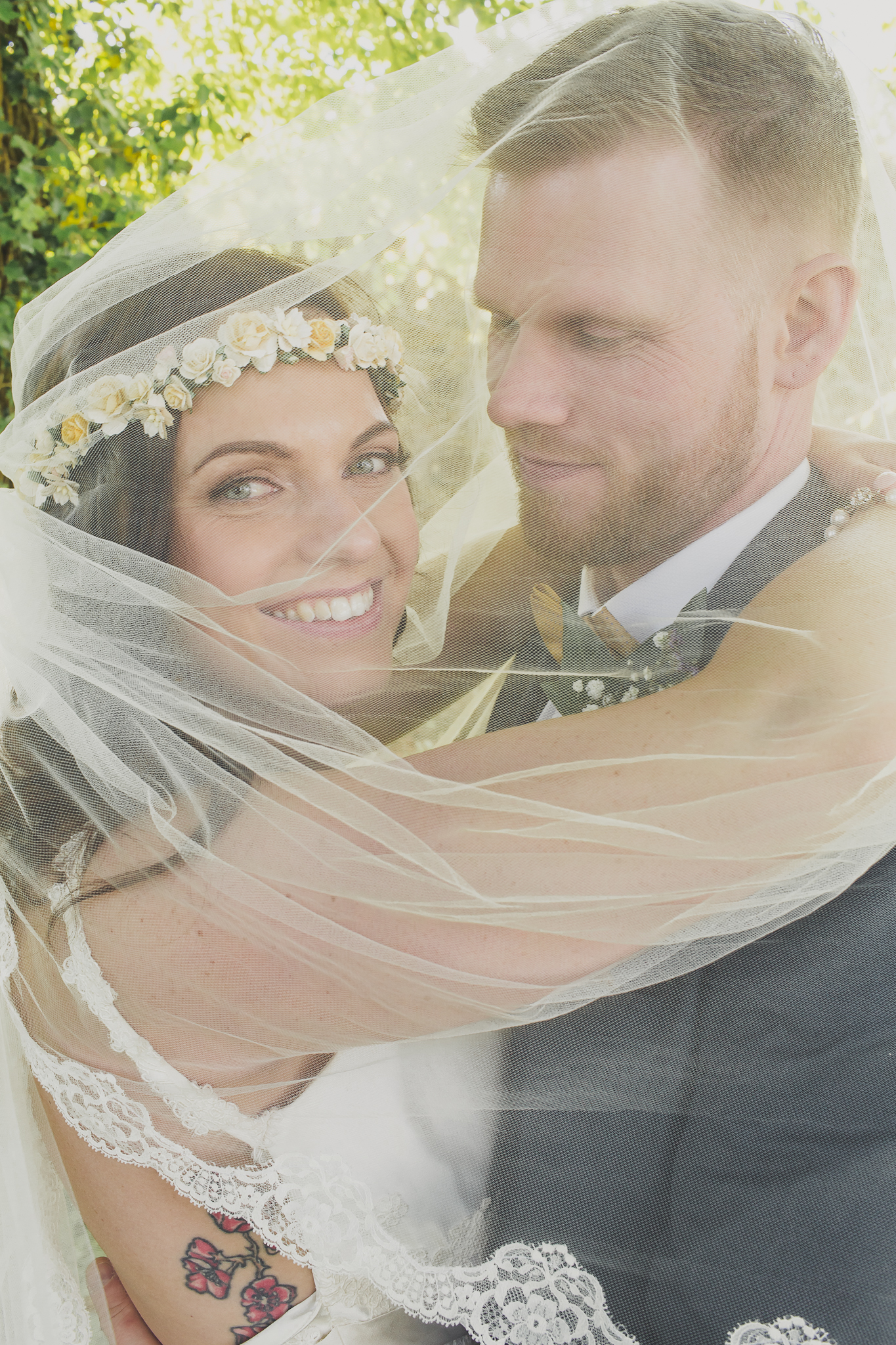 Picture of bride and groom on their wedding day. The bride is wearing her wedding dress with hair and makeup done.