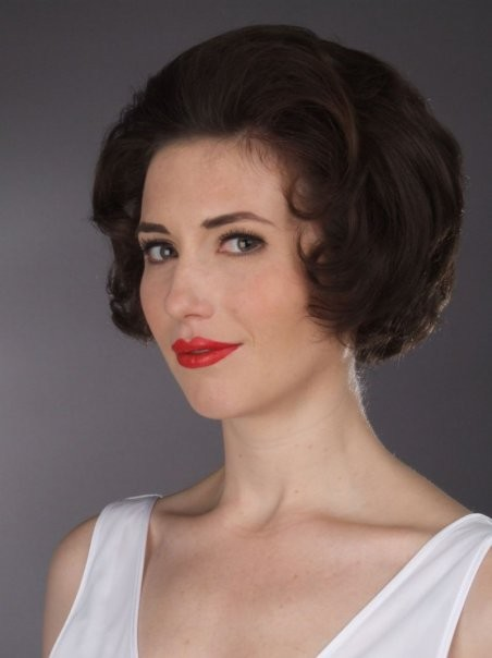 Picture of woman in vintage style makeup. She has 50's hair and red lipstick