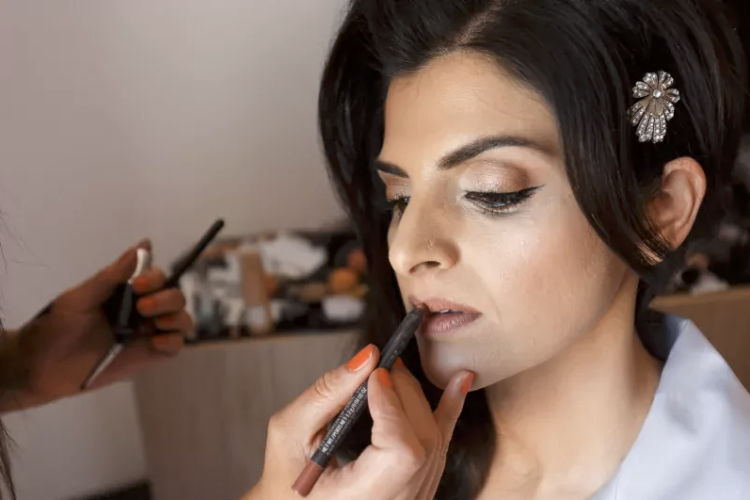 Image of bride getting lipstick applied by her makeup artist