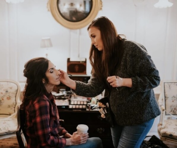 Image of bride getting mascara applied by her makeup artist